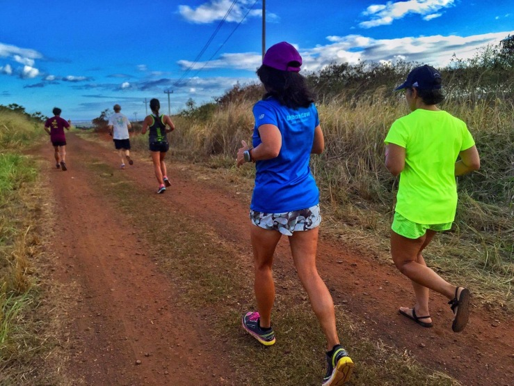 Runners on a dirt track, back view. Blue sky, clouds, telephone poles on the right, dried grass on both sides of the track.