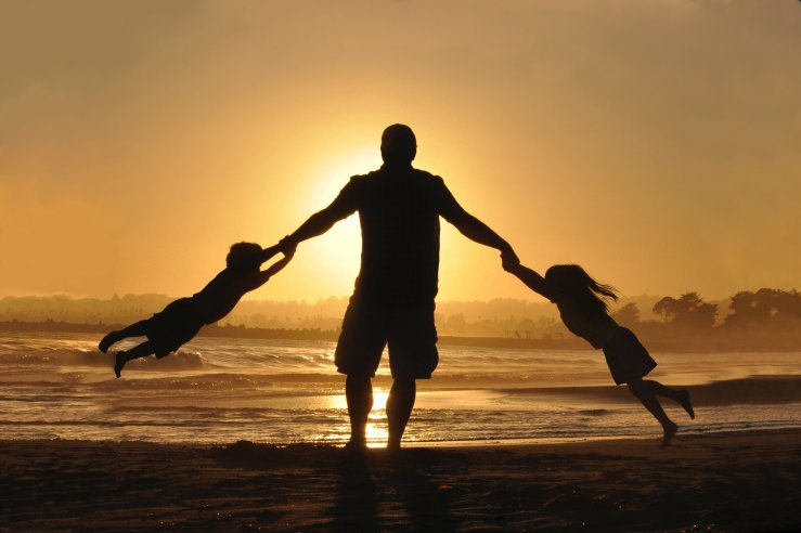 Silhouette of man swinging a girl and boy around in each arm at the beach. Yellow glow of sunset in background.