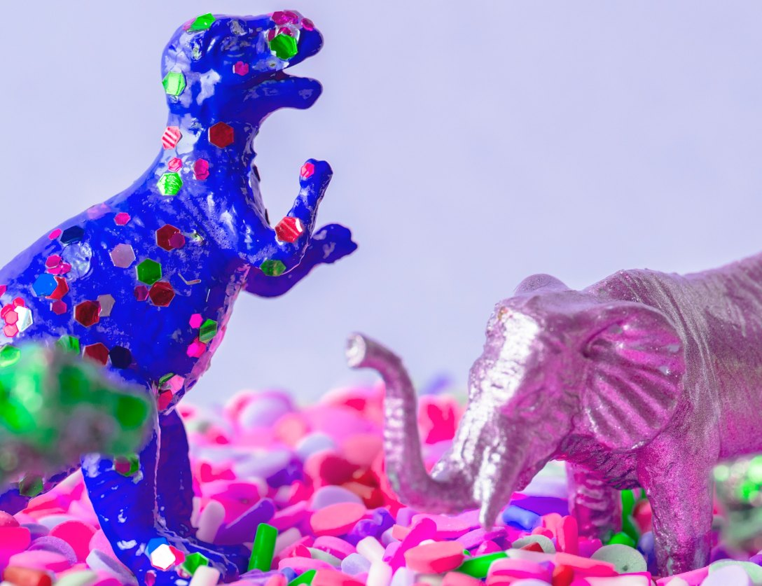 blue sparkly tyranosaurus rex toy and pink shiny elephant toy standing in pink, purple, green, and white pills