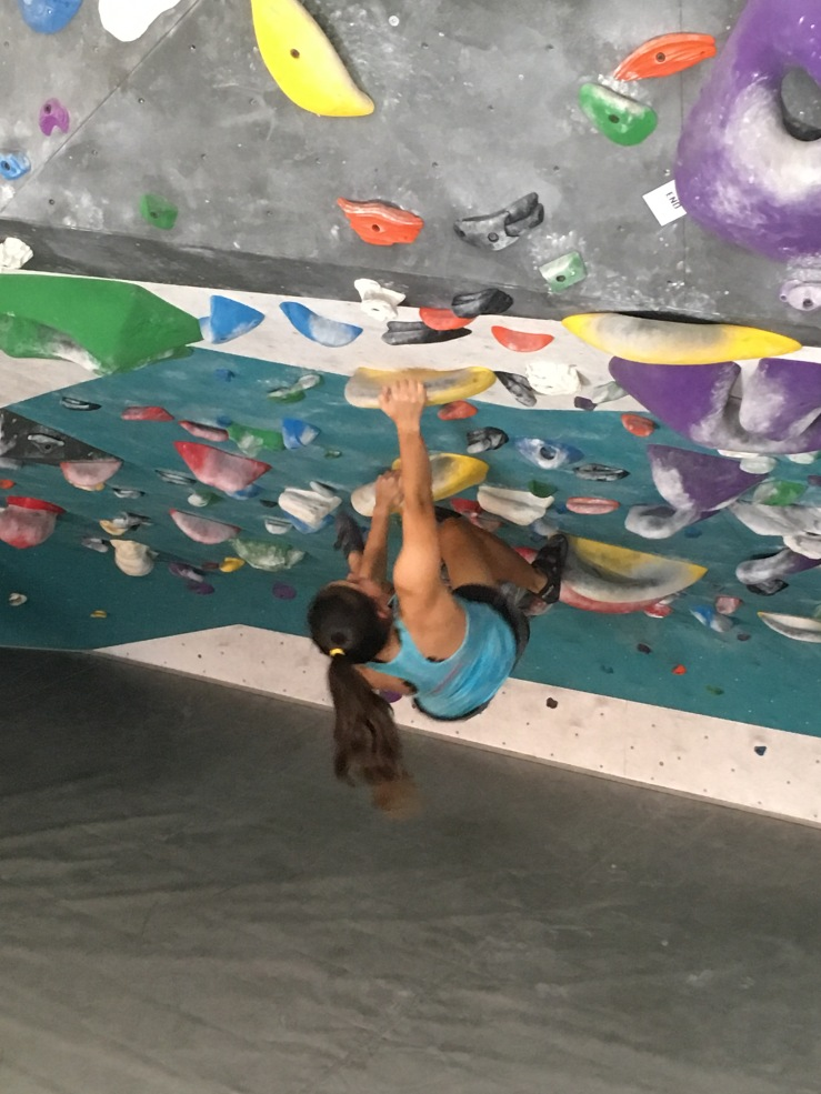 Long ponytail female climbing an inclined indoor climbing wall