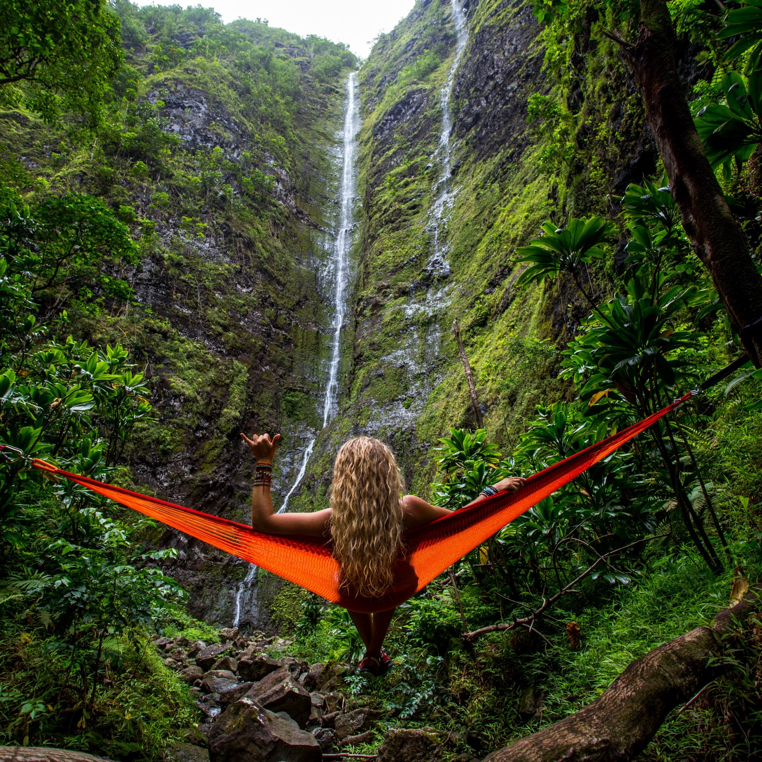 back view of long, wavy, sun-bleached blond-haired girl sitting in orange hammock in front of waterfall with trickling flow, green moss all over the mountain in front of her, vibrant ti leaf plants and ferns all around, she is making a shaka sign with her left hand, multiple bracelets on both wrists