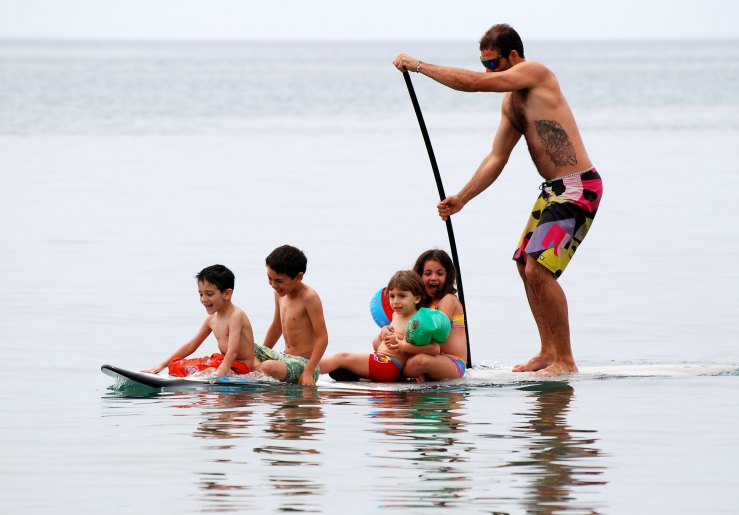 Dad stand-up paddle-boarding with 4  smiling kids