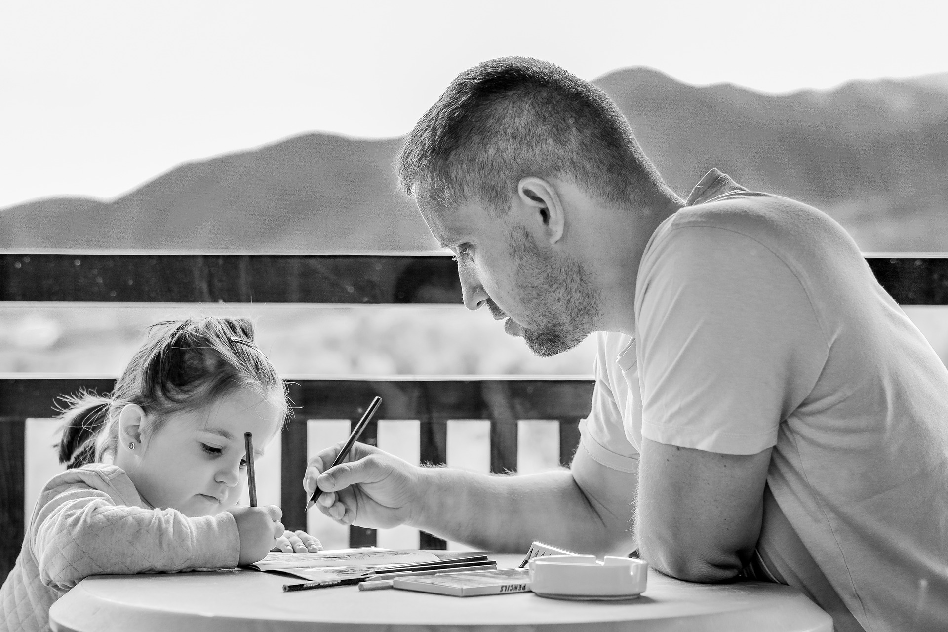 Black and white picture of toddler girl with hair tied back writing with right hand and sitting at a round table opposite t-shirt wearing dad holding pen in right hand
