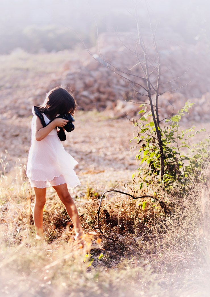 Brown-haired girl in diaphanous white dress using real camera to photograph something near the ground, standing in a field of dry grass.
