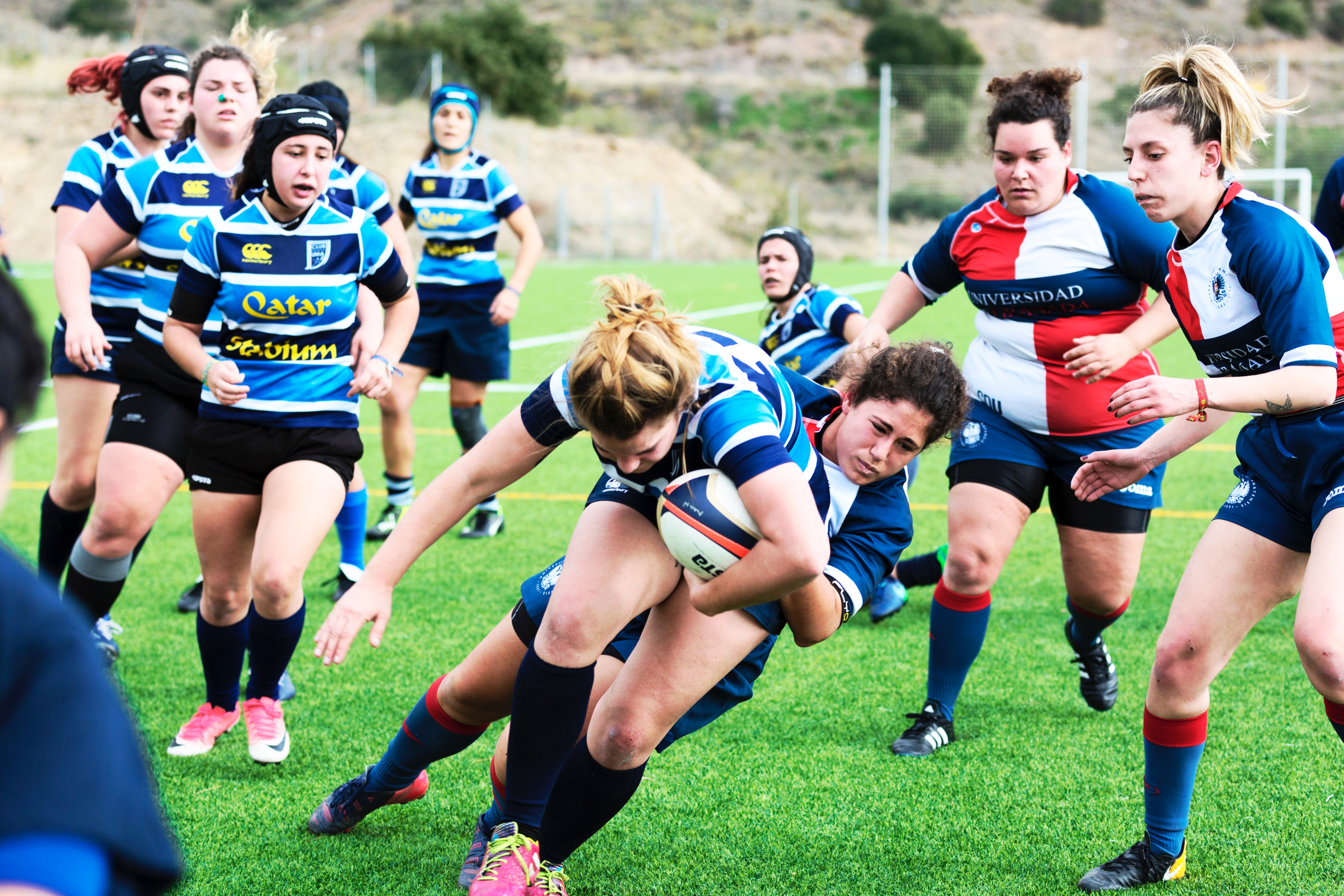 Women rugby players. One woman is tackling another player holding the ball. One team wears dark blue, white, and light blue striped shirts. The other team wears red, white, and navy shirts.
