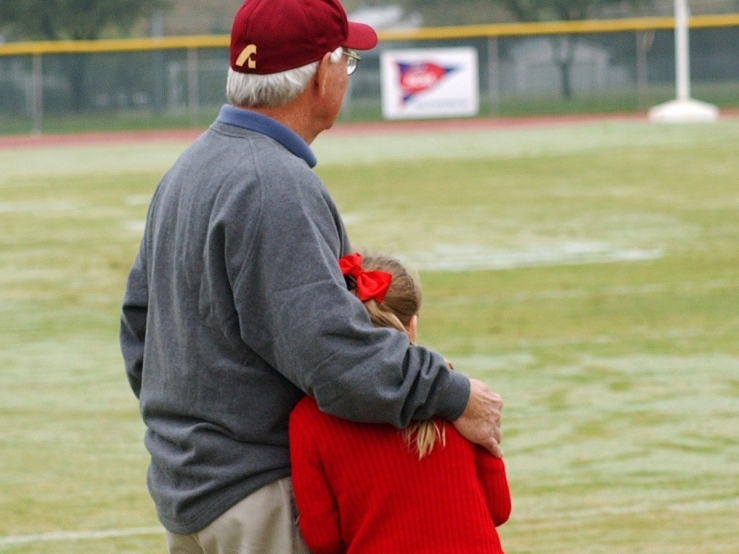 white-haired man in maroon baseball cap, grey sweater, tan pants holding girl wearing red hair bow, red long-sleeved shirt and black pants on sidelines of American football field