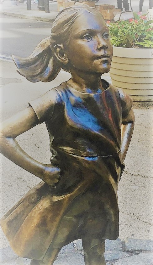 Bronze statue of a girl in a dress and ankle boots and medium length hair. Confident expression and hands on hips.