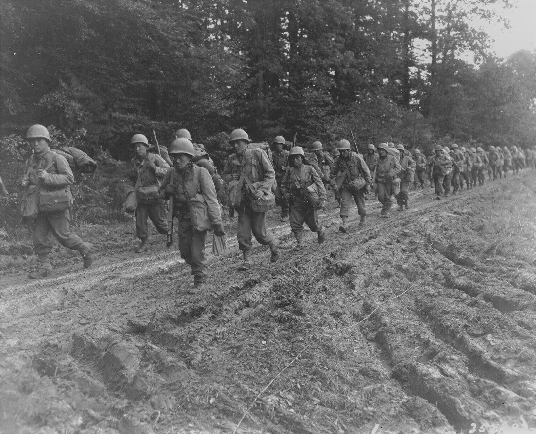 Asian American World War 2 soldiers marching on a dirt road