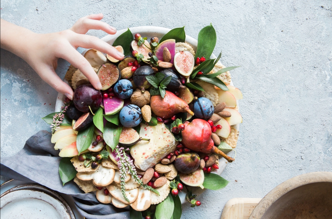 hand selecting from a dish full of fruits and nuts