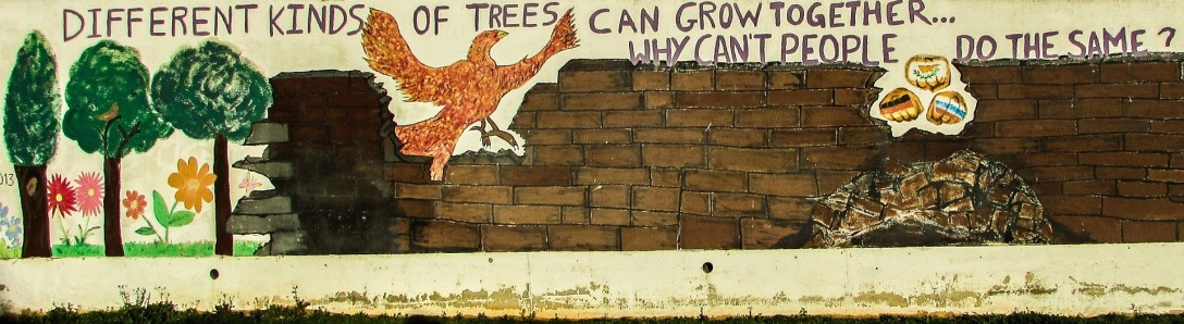 "mural with trees on left, brick wall with eagle flying through, ""Different kinds of trees can grow together...why can't people do the same?"""