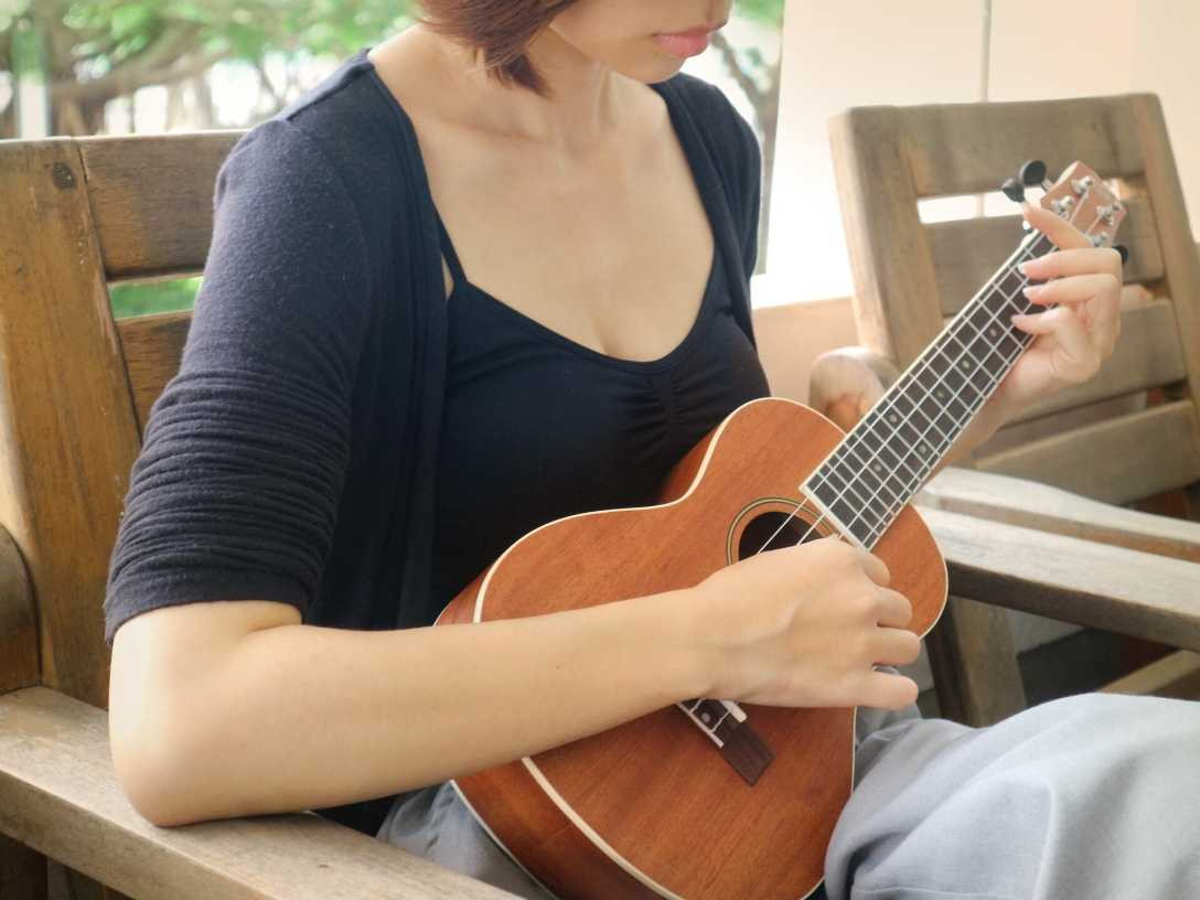 woman sitting in chair playing ukulele