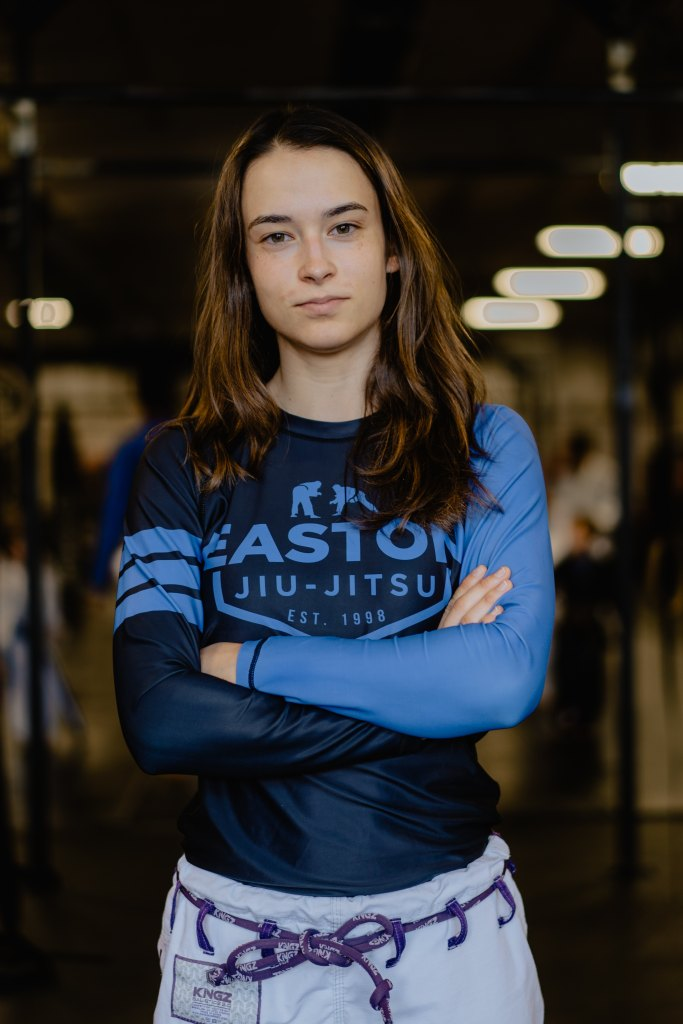 Young adult female with confident pose, arms crossed, wearing jiu-jitsu shirt and pants