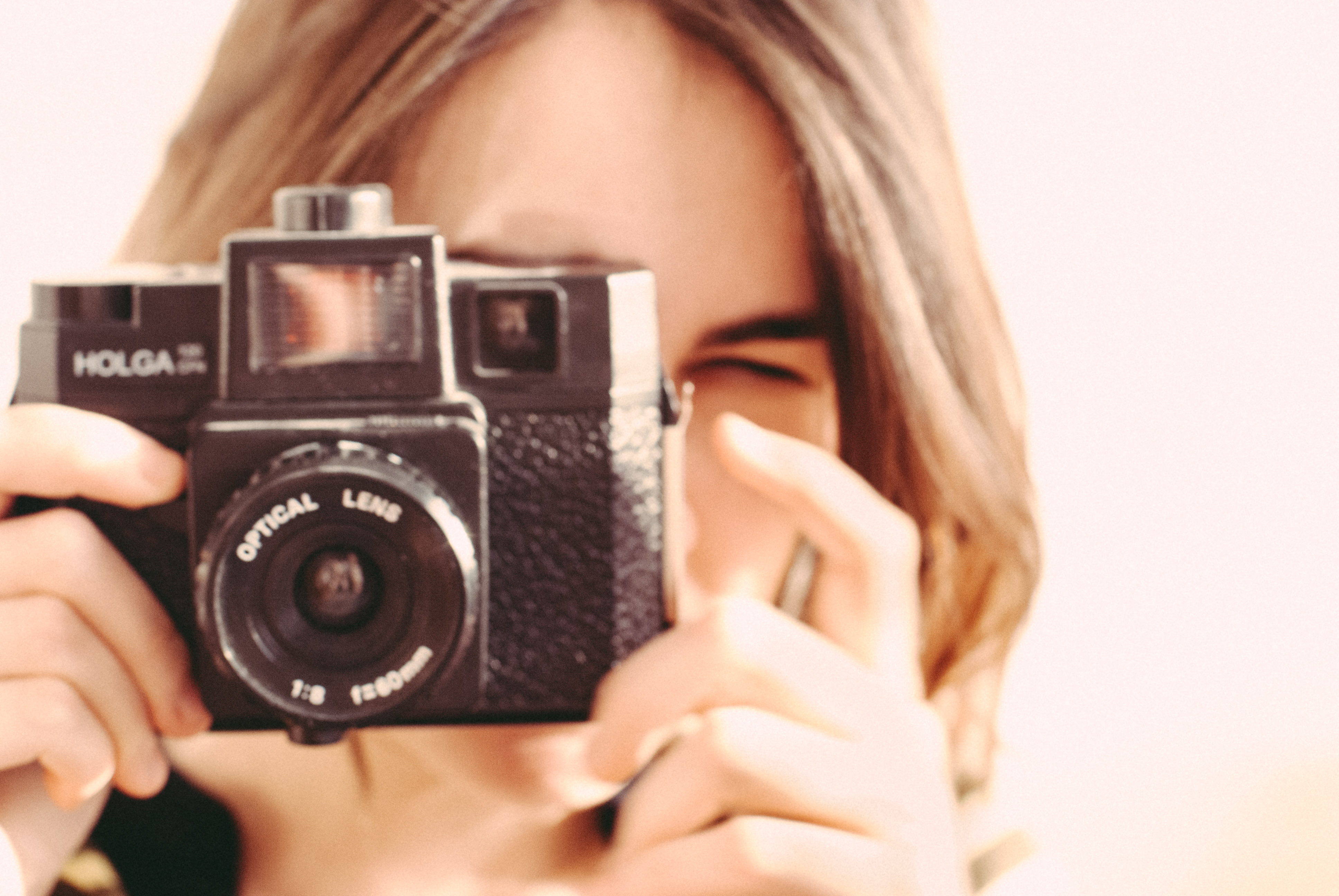 brown-haired person squinting into Holga brand camera (old fashioned kind)
