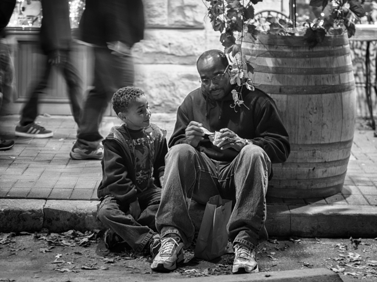 Black father and son sitting on the sidewalk sharing ice cream