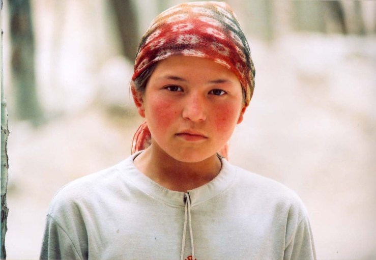 Uyghur girl with colorful head covering and white tunic