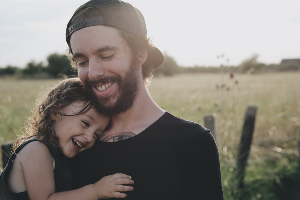 father holding young daughter in field, both smiling