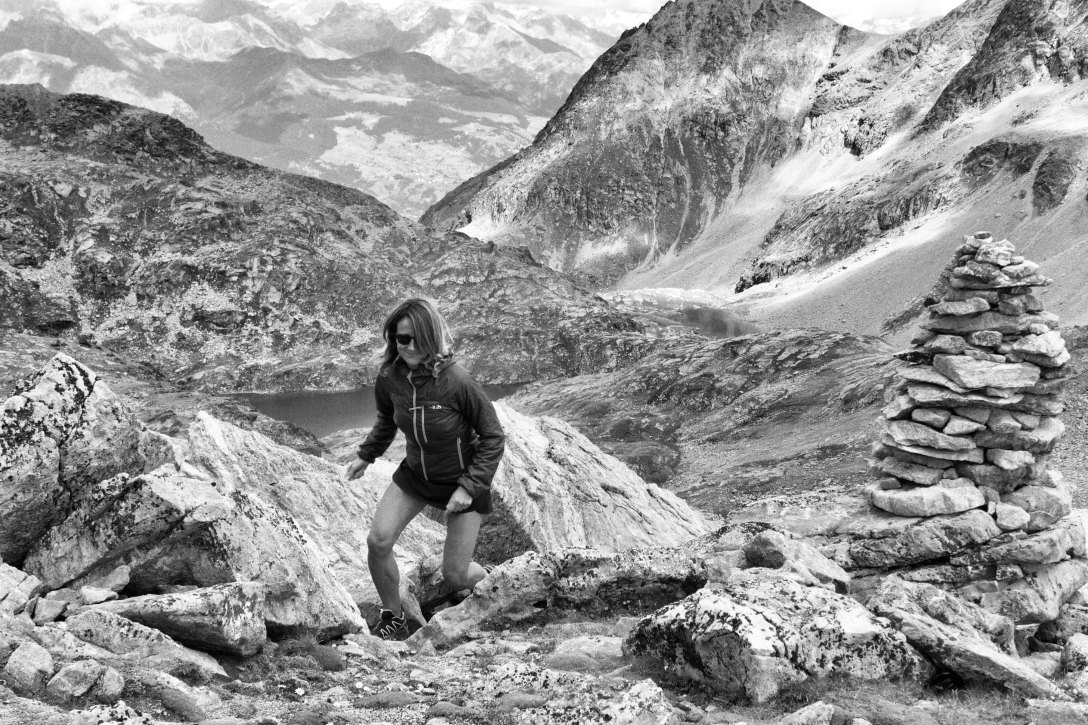 black and white photo of female runner in rocky, dry mountains