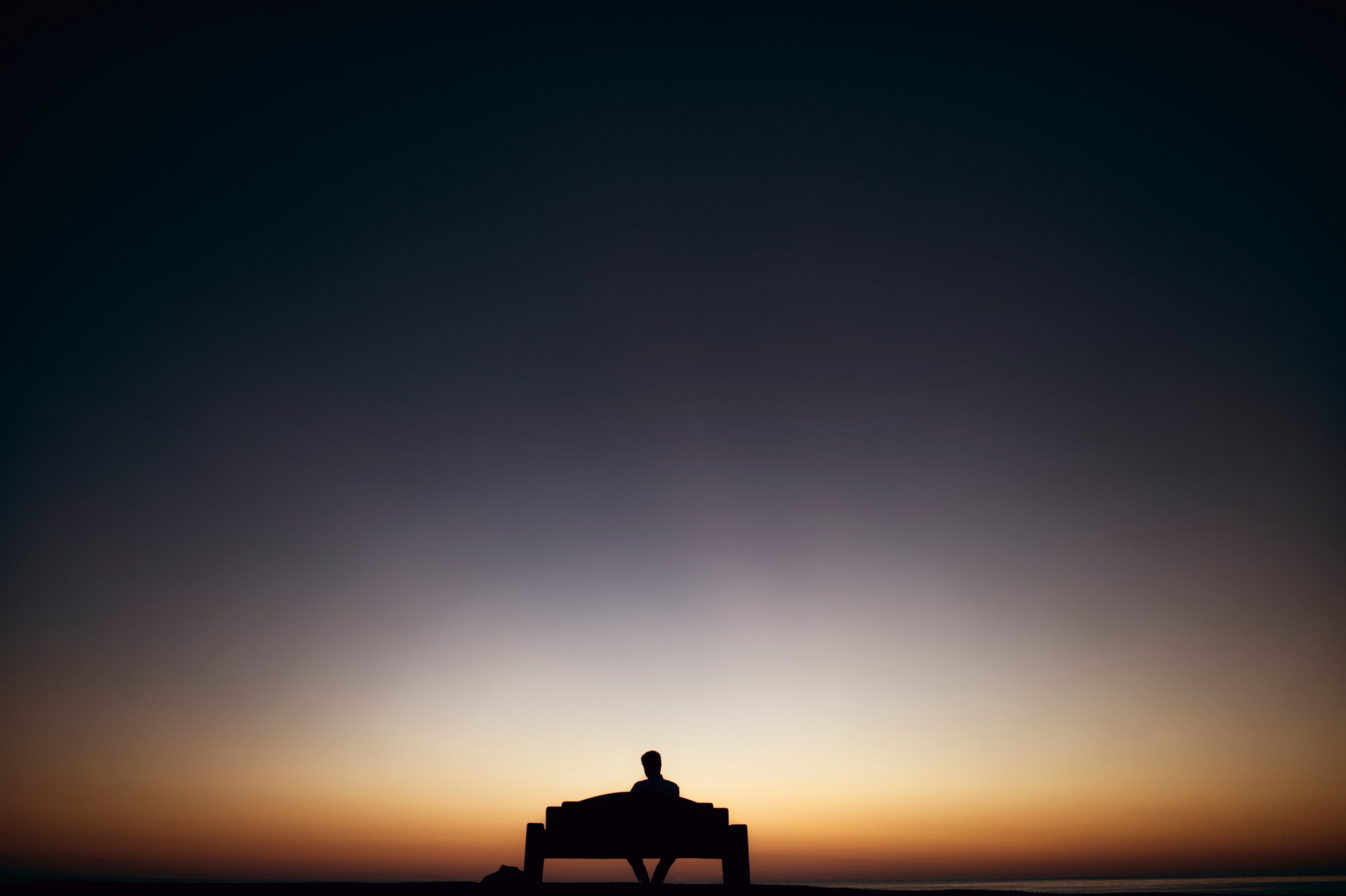 Silhouette of person sitting alone on a bench in the distance