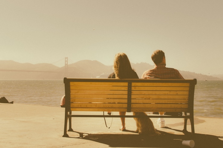 Back view of two people sitting on park bench not talking to each other with dog sitting beneath