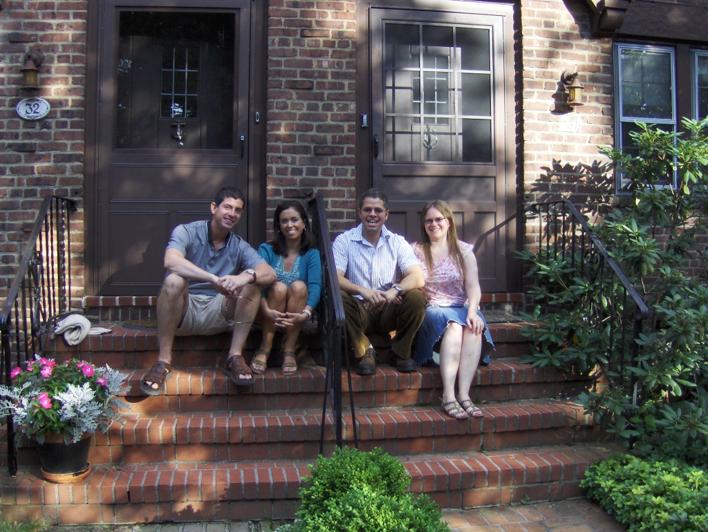 two couples, neighbors, sitting next to each other on front steps of their duplex