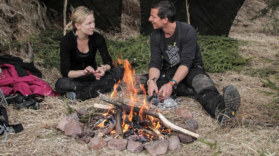 Bear Grylls talking with Kate Hudson next to a campfire