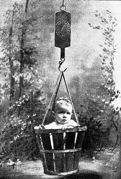 sad baby sitting in wooden bucket being weighed