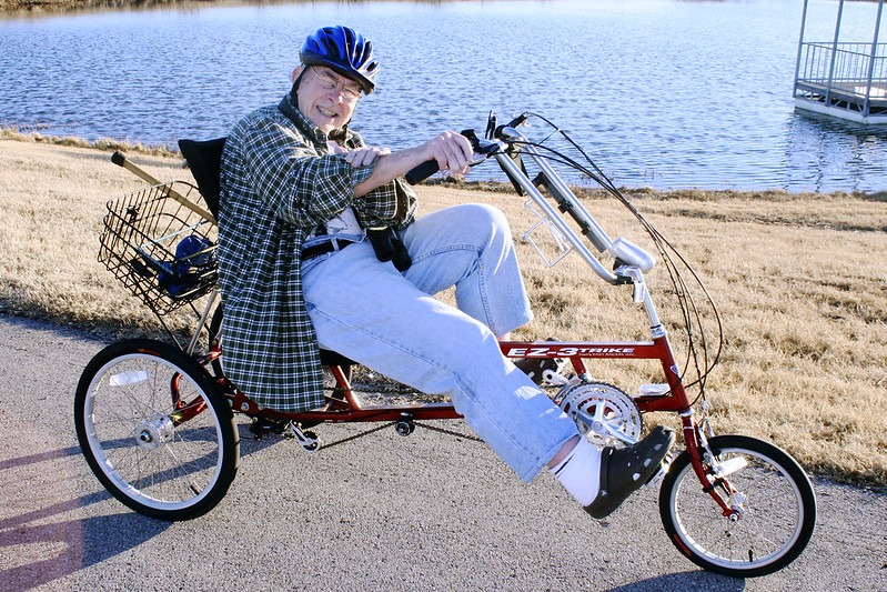 smiling elderly man wearing bike helmet and riding adult tricycle with basket