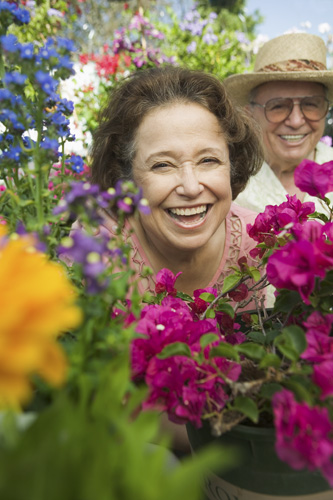 smiling older couple with flowers in the foreground