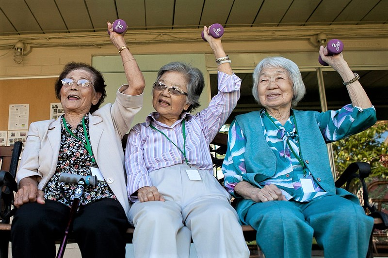 three seated elderly women holding up a weight in their left hands