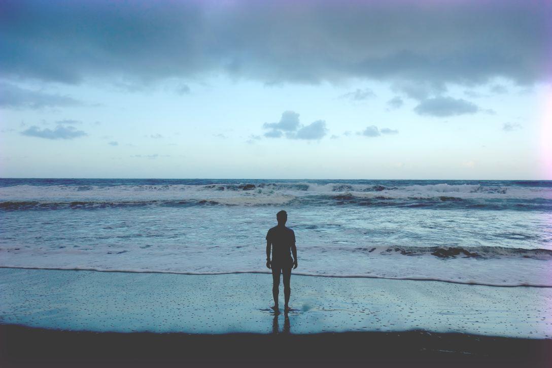 silhouette of man at shorebreak at dawn or dusk