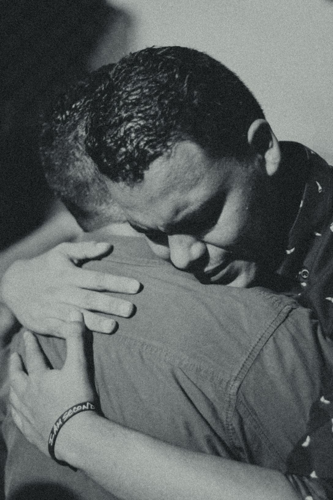 black and white photo of two men hugging
