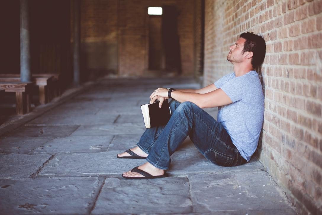 man sitting on ground against brick wall, eyes closed, holding a book